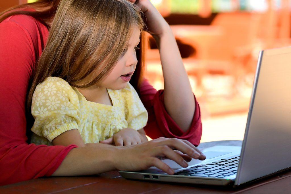 Child sitting on mother's lap while playing on the computer