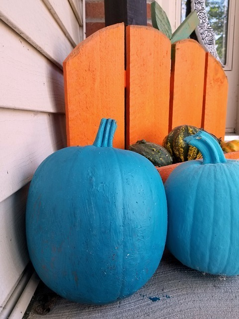 Teal pumpkins in front of an orange chair