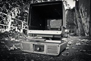 A really old, broken computer in an alley with leaves on the ground